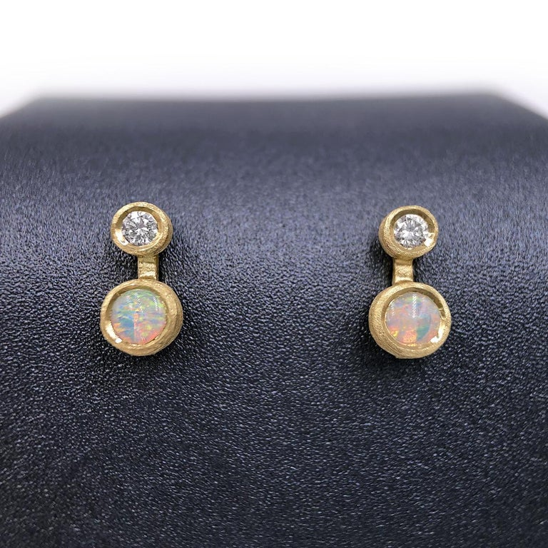 Nova Stud Earrings handcrafted in London by jewelry artist Shimell and Madden in satin-finished 18k yellow gold with 0.08 total carats of round brilliant-cut white diamonds and a matched pair of Australian opal cabochons, all bezel-set and attached
