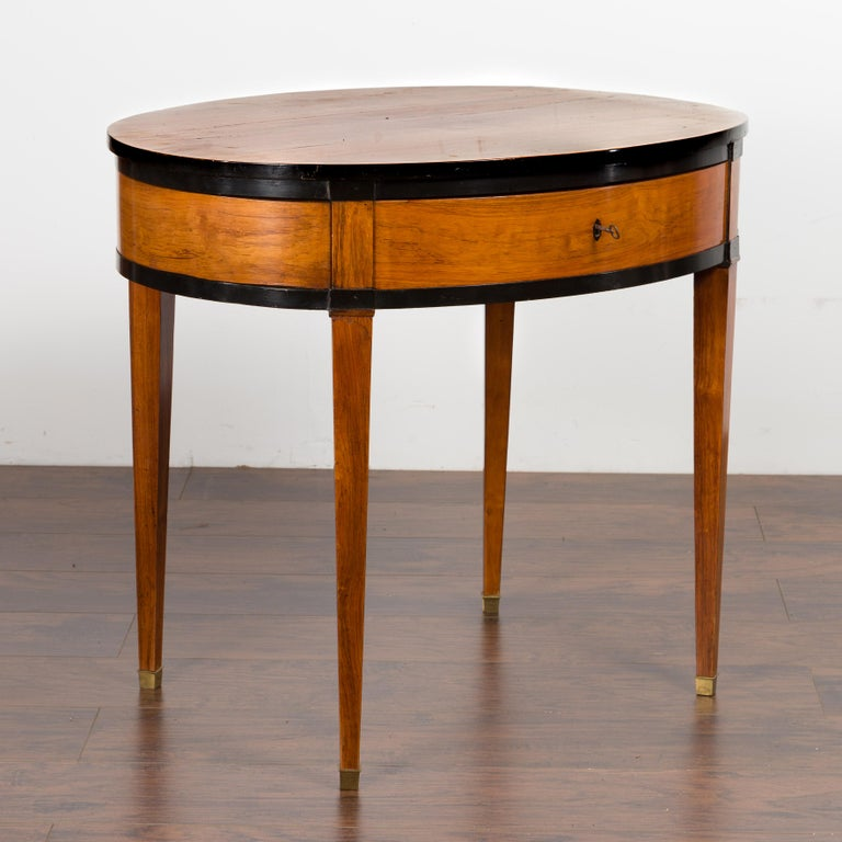 An Austrian Biedermeier period oval top table from the mid-19th century, with ebonized accents and single drawer. Created in Austria during the second quarter of the 19th century, this Biedermeier table features an oval top sitting above a single