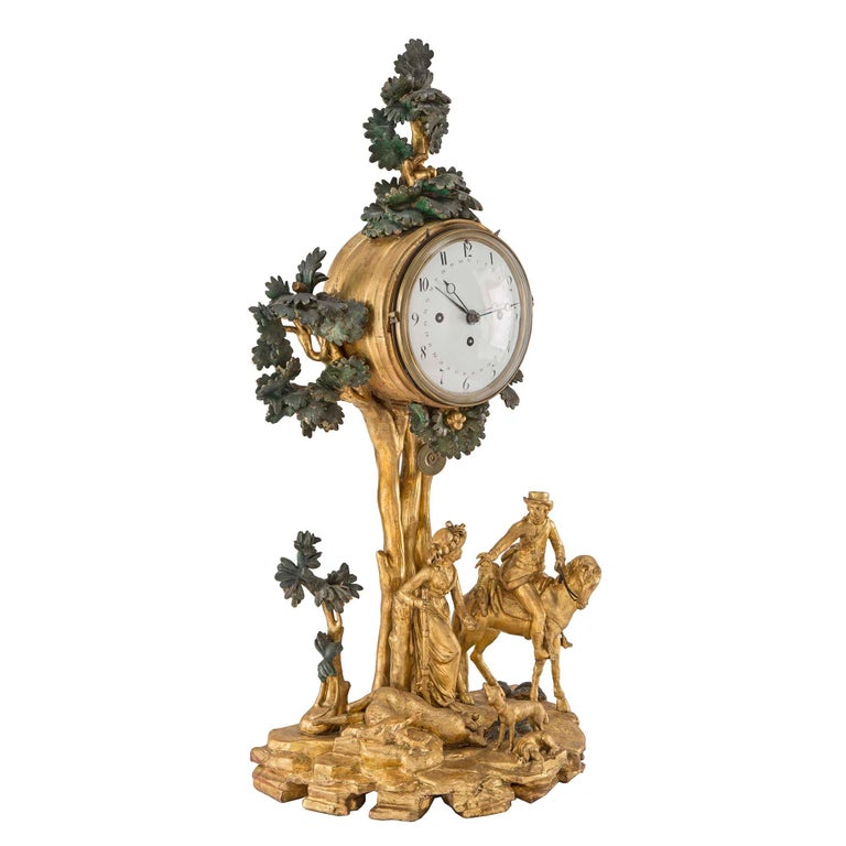 A very unique Austrian 18th century giltwood and polychrome clock, with the original Grand Sonnerie movement. At the base is a country scene of a lady holding a rifle. At her feet are two dogs and a hunters spoils, and a man on a horse beside her. A