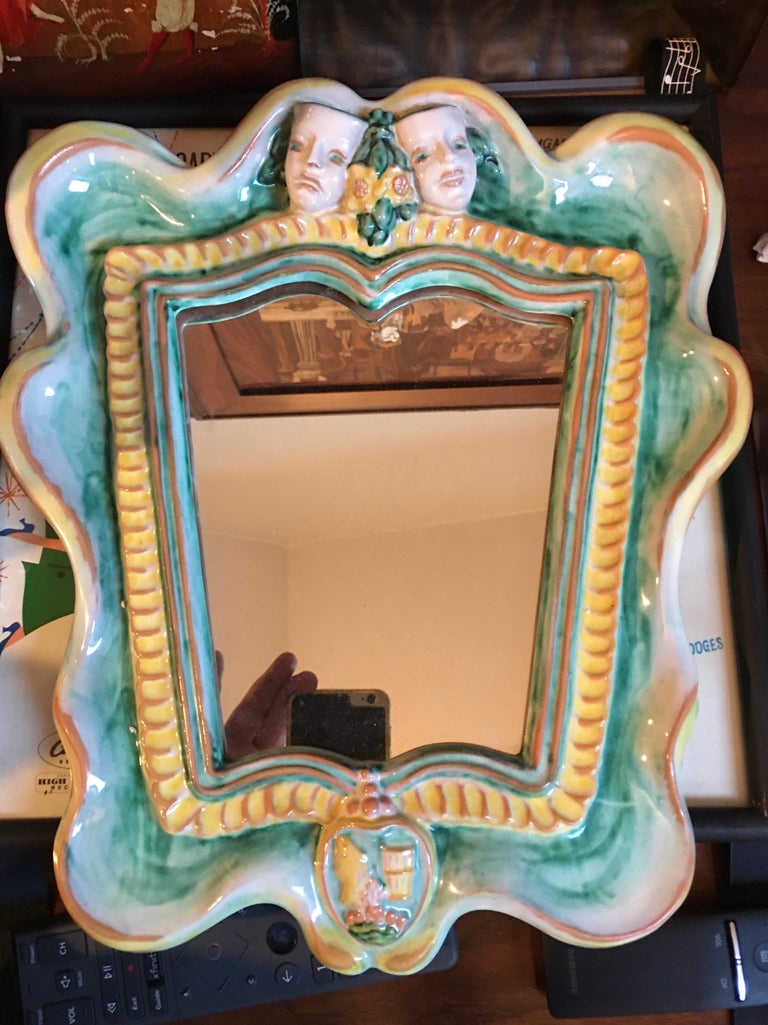 Franz Schleiss (1884-1969) for Gmundner Keramic, Austria 1930s wall mirror, Model 2140, green, yellow and red glaze. Shield-shaped frame, above two sculpted theatrical masks with a bouquet of flowers below a decorative coat of arms.