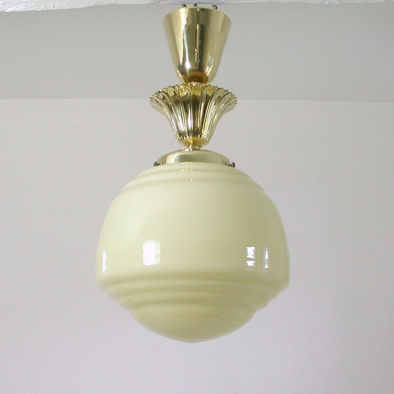 This late Art Deco ceiling light was designed and manufactured in Austria in the early 1940s. It has got an ivory colored opaline glass shade and brass details. All brass parts have been polished and the lamp has been rewired.