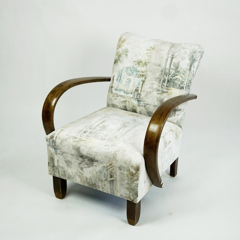 This charming and elegant Art Deco armchair has been completely restored and newly upholstered. The structure in beechwood features striking armrests that were curved using steam. The new upholstery is an ivory velvet wich shows classical