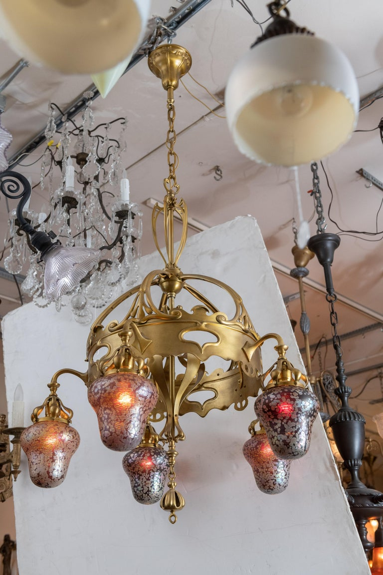 This chandelier is the essence of Art Nouveau with sinewy lines and about the best hand blown glass shades we have encountered in all our years of selling lighting. I guess the optimum word here is exotic in describing the Austrian glass here. The