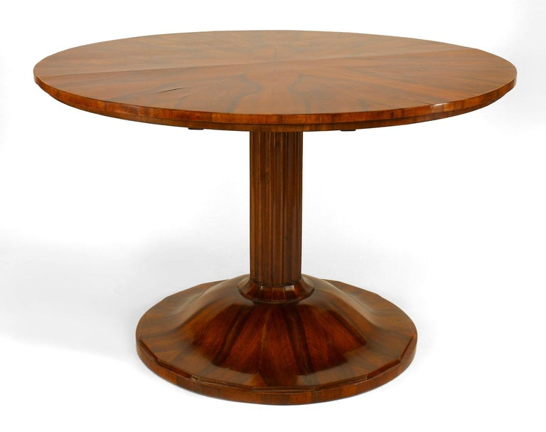 Round nineteenth century Austrian Biedermeier book matched walnut veneered center table supported by a fluted pedestal and a round, scalloped platform base.
