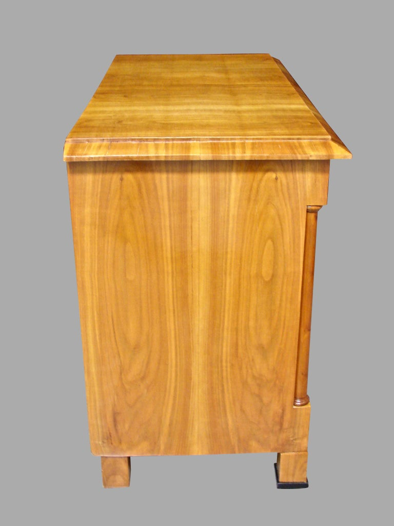 A good quality Austrian Biedermeier polished fruitwood (probably cherry) commode with figured well-matched veneers, the overhanging top above 3 long drawers framed by columns, each with an ebonized keyhole escutcheon, resting on block feet with