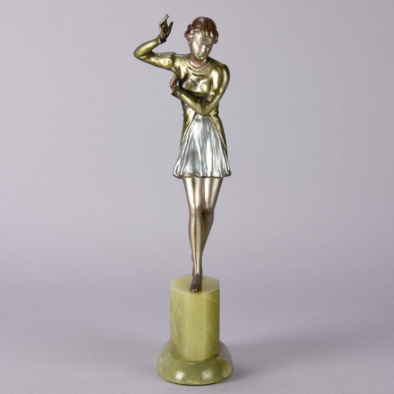 A highly attractive early 20th century Austrian Art Deco bronze figure of a beautiful young dancer in a winged costume standing on one leg in an elegant pose. The bronze with very fine vibrant cold painted colors and good surface detail, raised on a