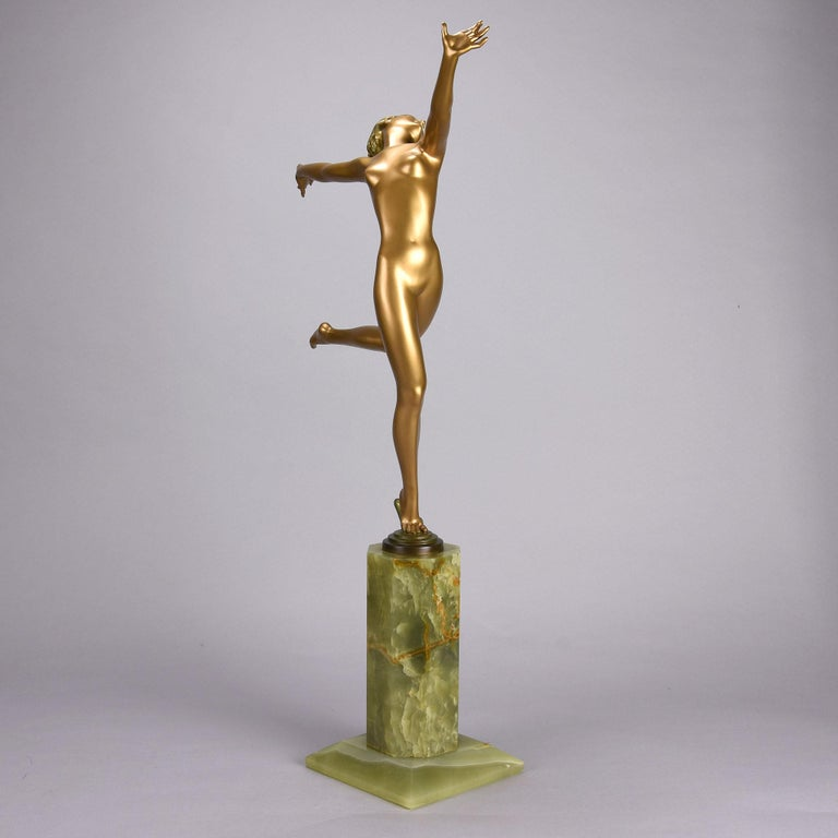 A fabulous and very large early 20th century Austrian Art Deco cold painted bronze figure of a naked dancer in a running pose with excellent golden color and very fine hand finished detail, raised on a tall onyx base and signed Lorenzl