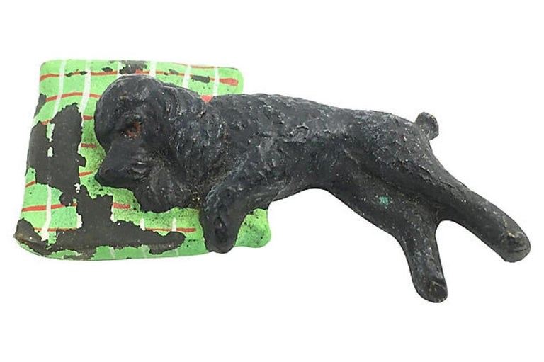 Austrian cold-painted bronze figurine of a sleeping poodle on a green, red, and white checked pillow. No maker's mark. Extensive paint loss on pillow.