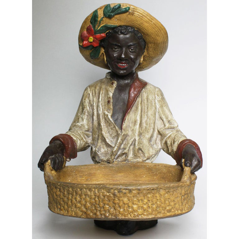 An Austrian early 20th century cast bust figure of an African girl holding a tray. The smiling young girl wearing a straw hat decorated with a flower and leaves, holding weaved-wicker-like tray, probably by Goldscheider's Porzellan-Manufactur and