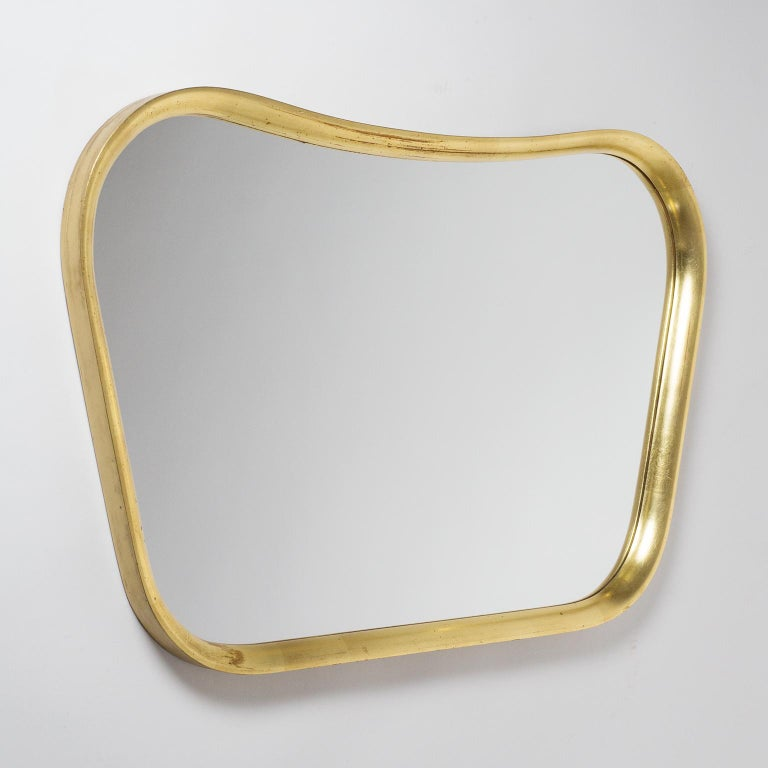 Lovely Austrian giltwood mirror from the late 1940s or early 1950s. Curved and sculpted solid wood frame with leaf gold finish. Nice vintage condition with some wear to the gilding and dryness to the wood.