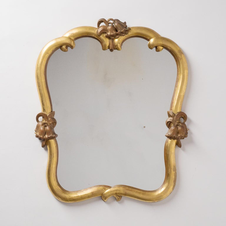 Rare pair of giltwood mirrors by Max Welz, circa 1930. Carved limewood with leaf gold and floral decorations - noteworthy is that the floral decor on the top are mirrored. Very good condition (previously retored frames and backplate) with original