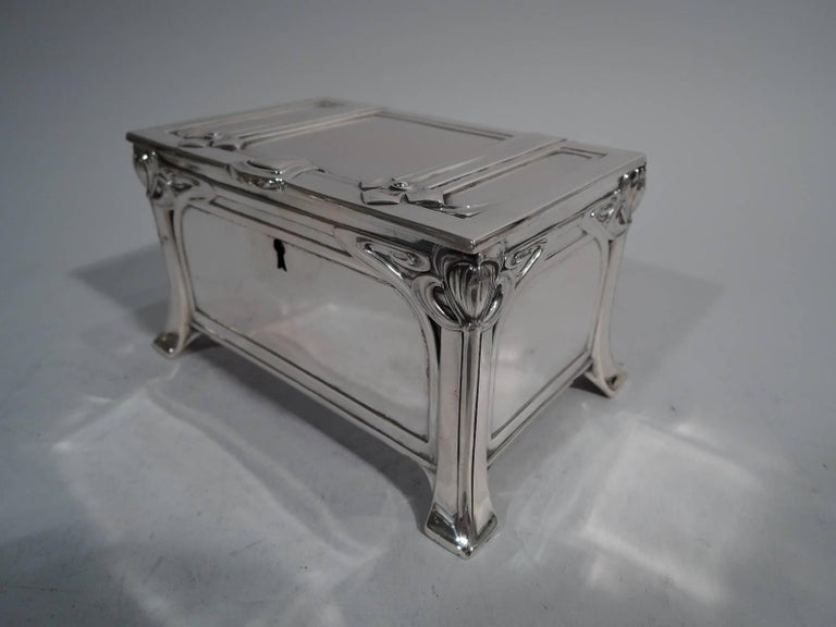 Austrian Jugendstil casket in 800 silver. Rectangular with straight sides, flat hinged cover, and splayed block supports. Sides and cover paneled. Ornament stylized and curvilinear. Sides have corner flowers between whiplash lines. Cover has straps