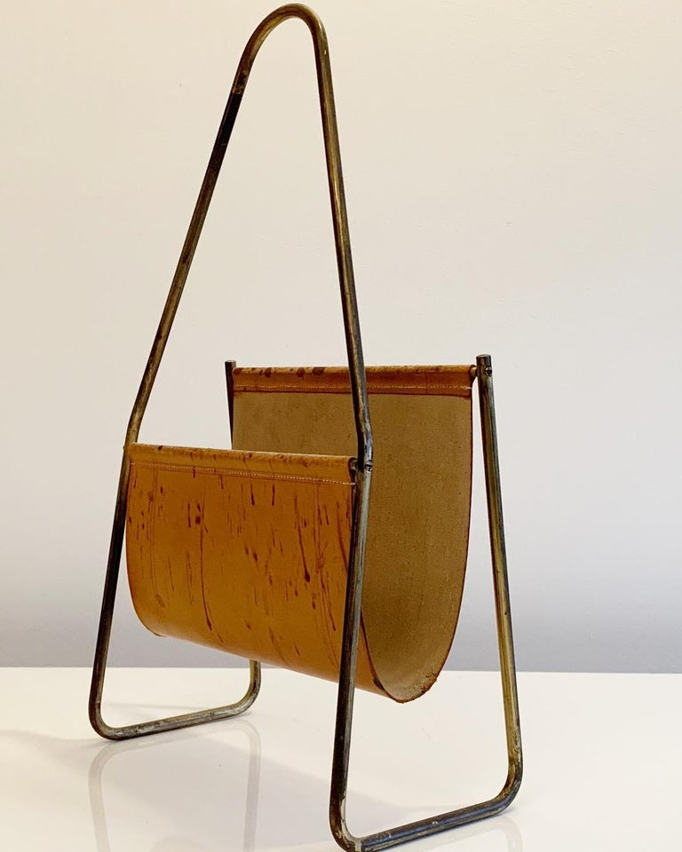 The fourth-generation Viennese workshop of Carl Auböck combines traditional craftsmanship with modern design. Designed in the 1950s by Carl Auböck II, this modern accent piece features tan leather and a lustrous brass frame. The resulting sling