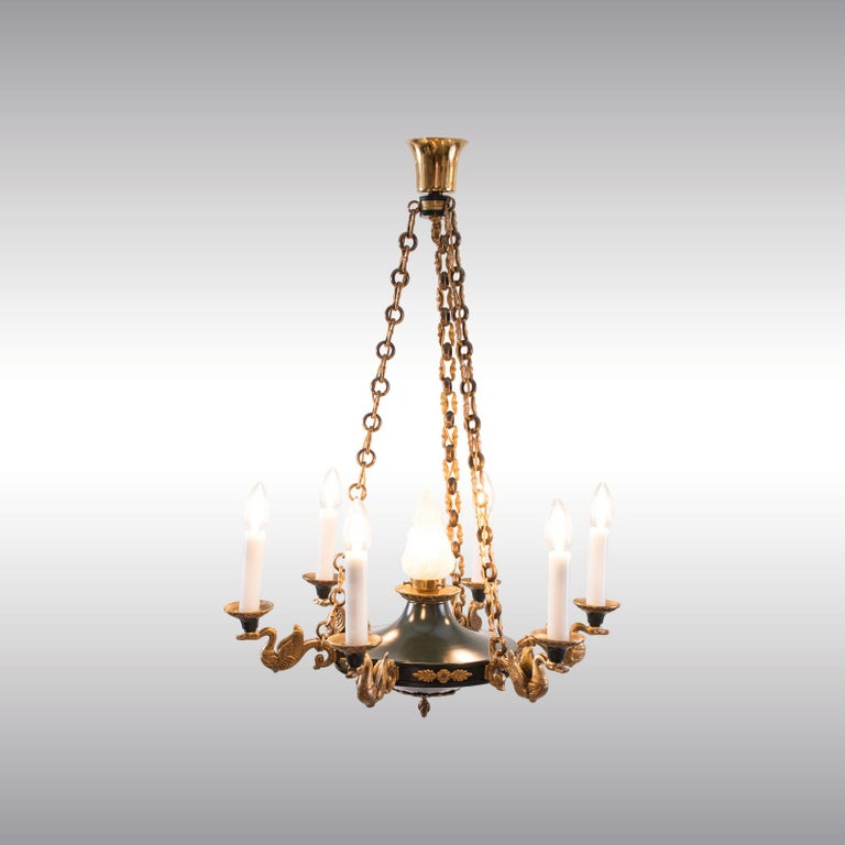 Very decorative chandelier in the style of Empire from the historistic Art Deco Period circa 1920. Stylized swans in gilded and punched casted brass.