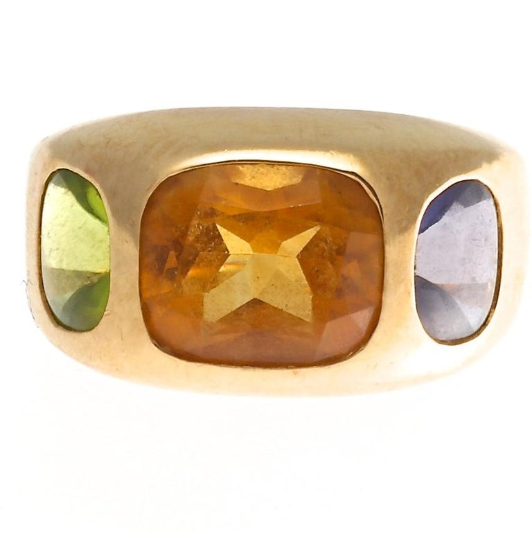 From the chic house of Chanel, a fabulous three stone ring with large faceted colored stones that look like candy. Featuring a 2.75 carat citrine in the center and a peridot and Iolite that are each 1 carat. This modern Chanel gemstone ring is a