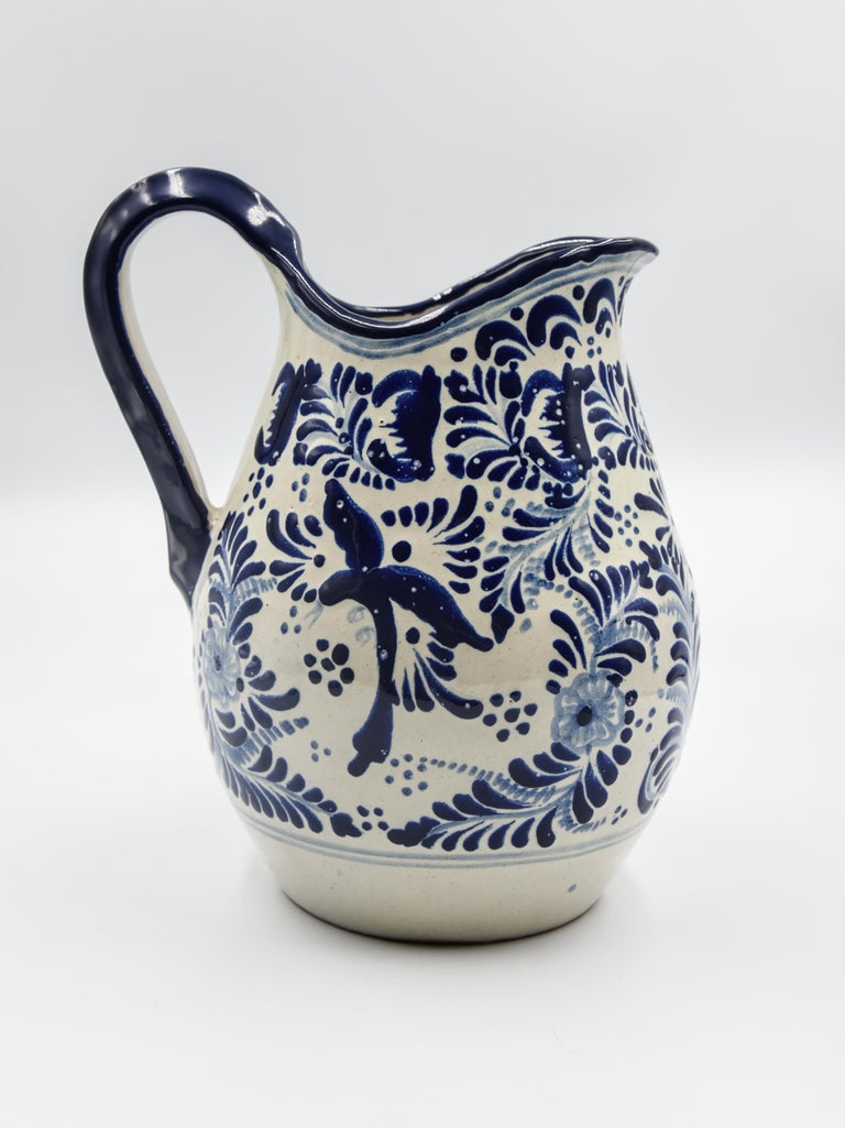 This elegant blue and white pitcher is made of Talavera. Perfect for a decorative piece or useful pitcher for the everyday life. Painted in a traditional poblano style this beautiful vessel is perfect for the kitchen or dinning room. 
