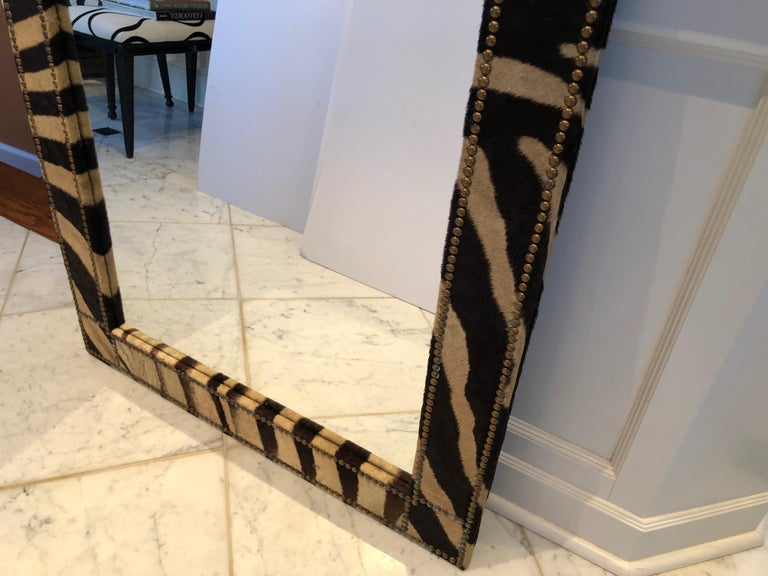 Super chic custom made mirror upholstered in zebra hide and finished with French antique brass nailheads. A pair is available.