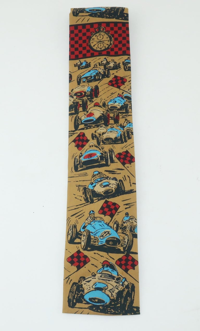 Rooster creates a hand printed cotton men's necktie with a novelty auto racing theme a la '24 Hours of Le Mans'.  The camel color background is accented with cars, drivers, checkered flags and stop watches all in shades of electric blue, red and