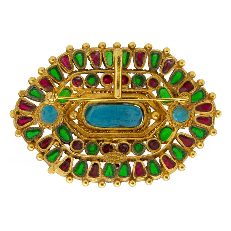 Beautifully detailed Chanel brooch from the Autumn 1993 collection. Slightly rounded hexagonal shape with twisted gold tone metal setting/details. The two outer perimeters are alternating red and green poured glass stones, with two small circular