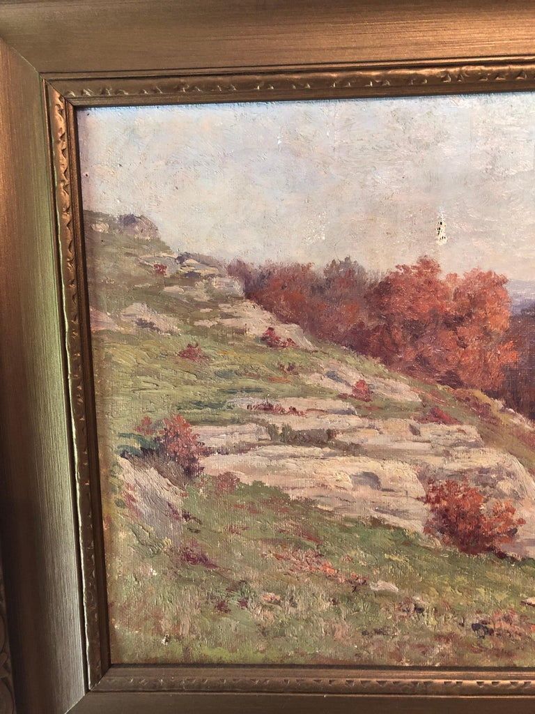 Impressionistic autumnal Massachusetts landscape painting featuring a rocky sloping Hillside with trees in peak foliage set against lavender mountains. Signed lower right margin M.E. Dickinson, 1911. Arts & Crafts gold painted cove moulded frame,