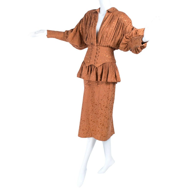 This is a rare Victorian style Norma Kamali skirt and jacket suit from the 1980's. This vintage Norma Kamali suit is iconic 1980's with shoulder pads and a cinched waist. The outfit is made in a copper jacquard fabric and the details are incredible.