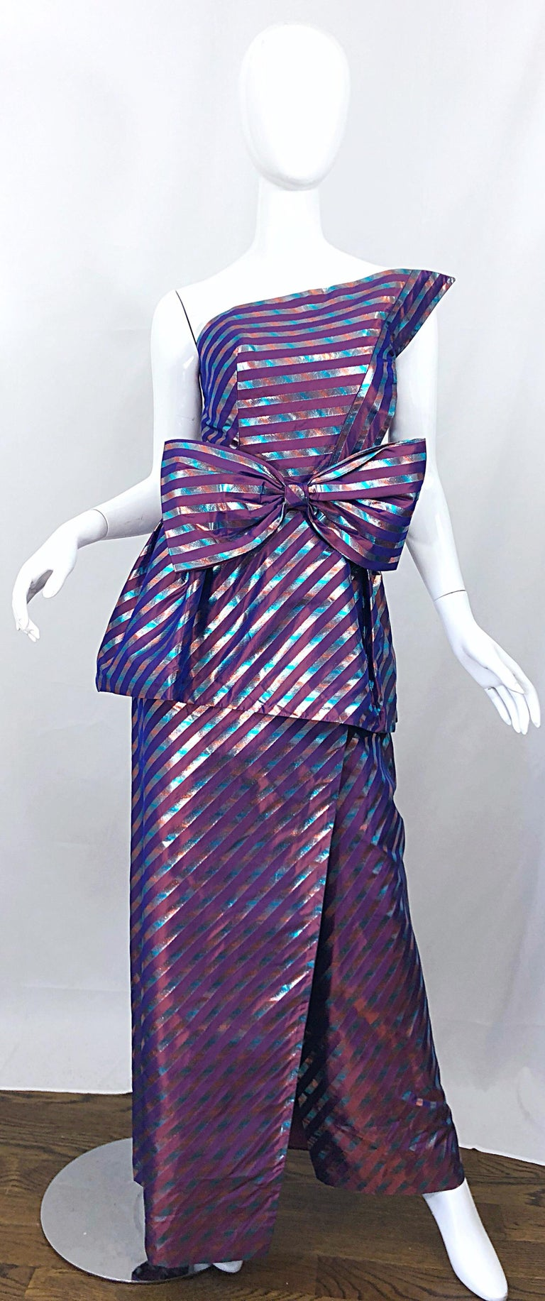 Beautiful 1980s RUBEN PANIS Couture for Eilzabeth Arden Avant Garde one shoulder metallic silk striped purple gown, with detachable bow belt! Beautiful iridescent purple, mixed with blue and pink flattering diagonal stripes throughout. Hidden zipper
