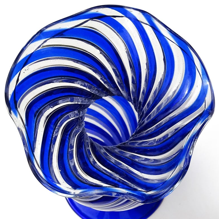 """Beautiful vintage Murano hand blown swirling cobalt blue and clear Italian art glass flower vase. Documented to Arte Vetraria Muranese (A.Ve.M.). Created in the """"A Canne"""" technique. It has a ruffled rim, and applied large foot. Would make a great"""