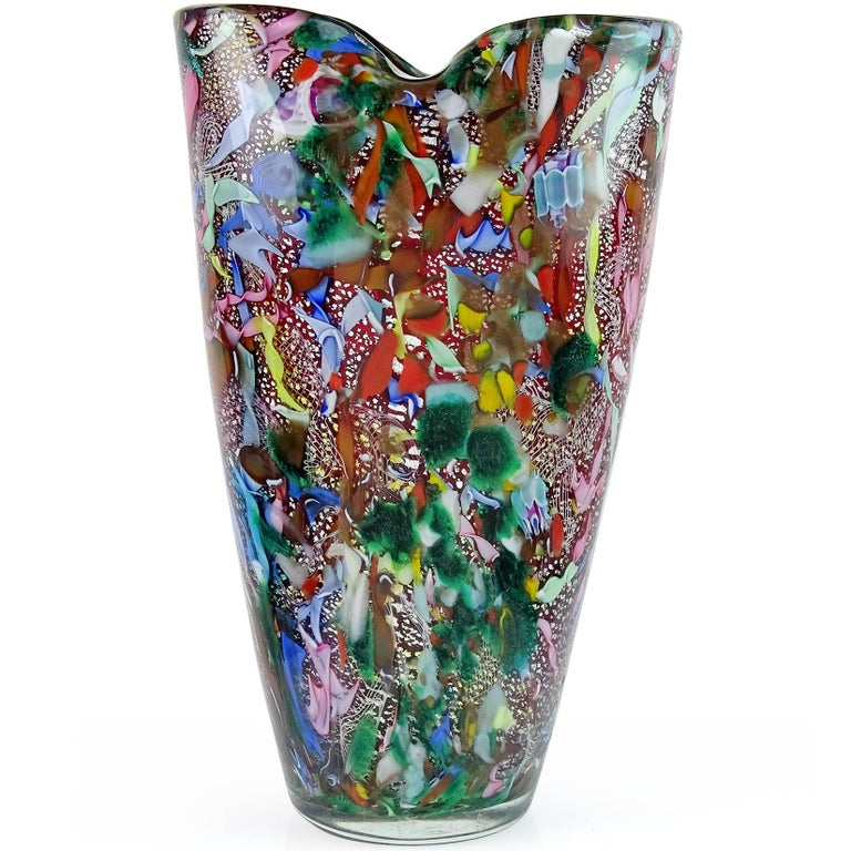 Beautiful vintage Murano hand blown red, silver flecks, green aventurine, millefiori murrines and twisted ribbons Italian art glass flower vase. Documented to the A.Ve.M. (Arte Vetraria Muranese) company. The piece has a pinched rim. Mid Century