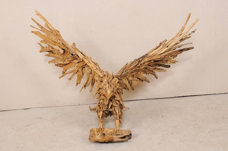 An awe-inspiring large-size eagle sculpture from driftwood. This majestic eagle is depicted with a broad upward wingspan, as if just landing or preparing for flight. The talons are gripped about a larger piece of wood, mouth closed, head straight.