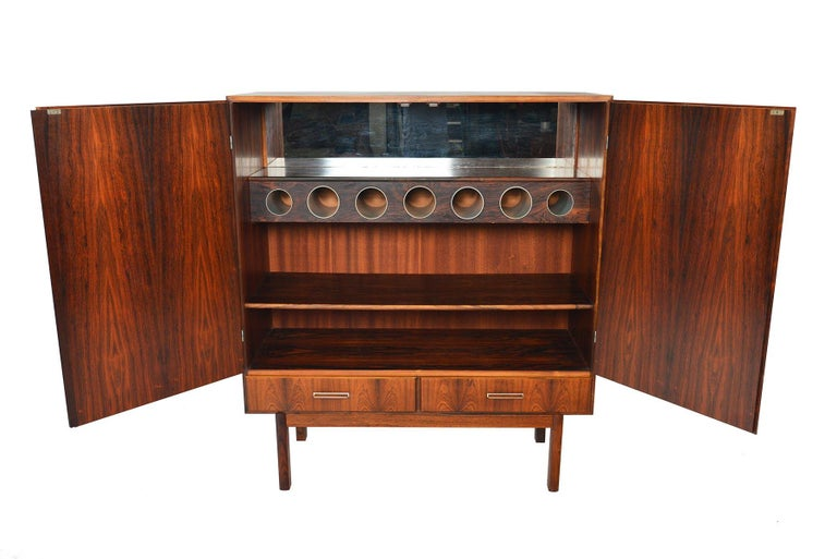 This large dry bar by Axel Christiansen Odder offers an impressive amount of storage and drama! Crafted in bookmatched Brazilian rosewood with aluminum handles, two large doors open to reveal a mirror lined interior, bottle storage, and an