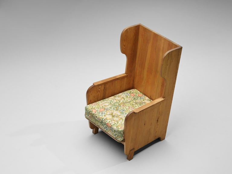Axel Einar Hjorth for Nordiska Kompaniet, wingback chair 'Lovo', in pine and fabric, Sweden, 1932  Sturdy high back chair in solid pine by Axel Einar Hjorth. This chair has all classical elements of a wingback chair, yet due the execution in