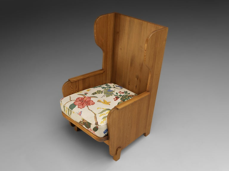 Axel Einar Hjorth for Nordiska Kompaniet, wingback chair 'Lovo', pine, floral fabric, Sweden, 1932  Sturdy high back chair in solid pine by Axel Einar Hjorth. This chair has all classical elements of a wingback chair, yet due the execution in