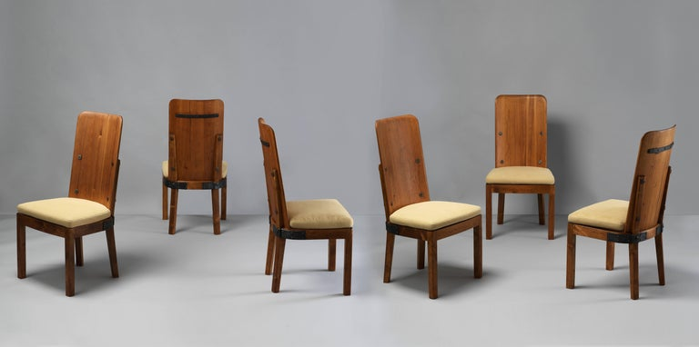 A set of six Lovö dining chairs by Axel Einar Hjorth, produced by Nordiska Kompaniet in the early 1930:s. Executed in pine and fortified by cast iron, giving the chairs a near Brutalist expression. Loose cushion seats in a brand new beige fabric.