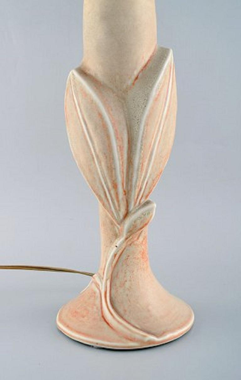 Axel Salto for Royal Copenhagen. Table lamp of stoneware modelled with leaves and branches in relief. Beautiful light yellowish glaze with orange elements. Designed in 1944.
