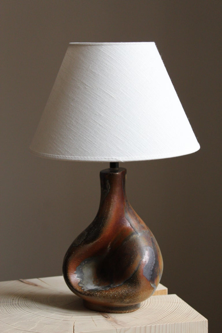 A table lamp produced and designed by Axella, Denmark, 1960s. With maker's label.  Lampshade is attached for reference and are not included in the purchase. Measured without lampshade.  Other ceramicists of the period include Axel Salto, Arne