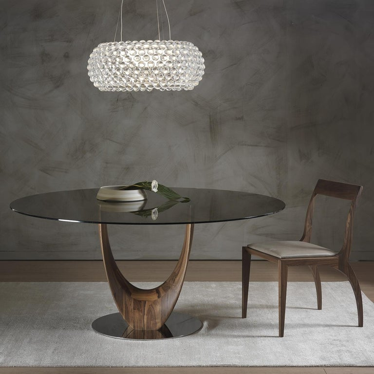 This elegant and modern dining table designed by Stefano Bigi features a stunning base in solid Canaletto walnut. The structure rests on a round element in chrome-plated metal and curves to form two separate legs that create a delicate sense of