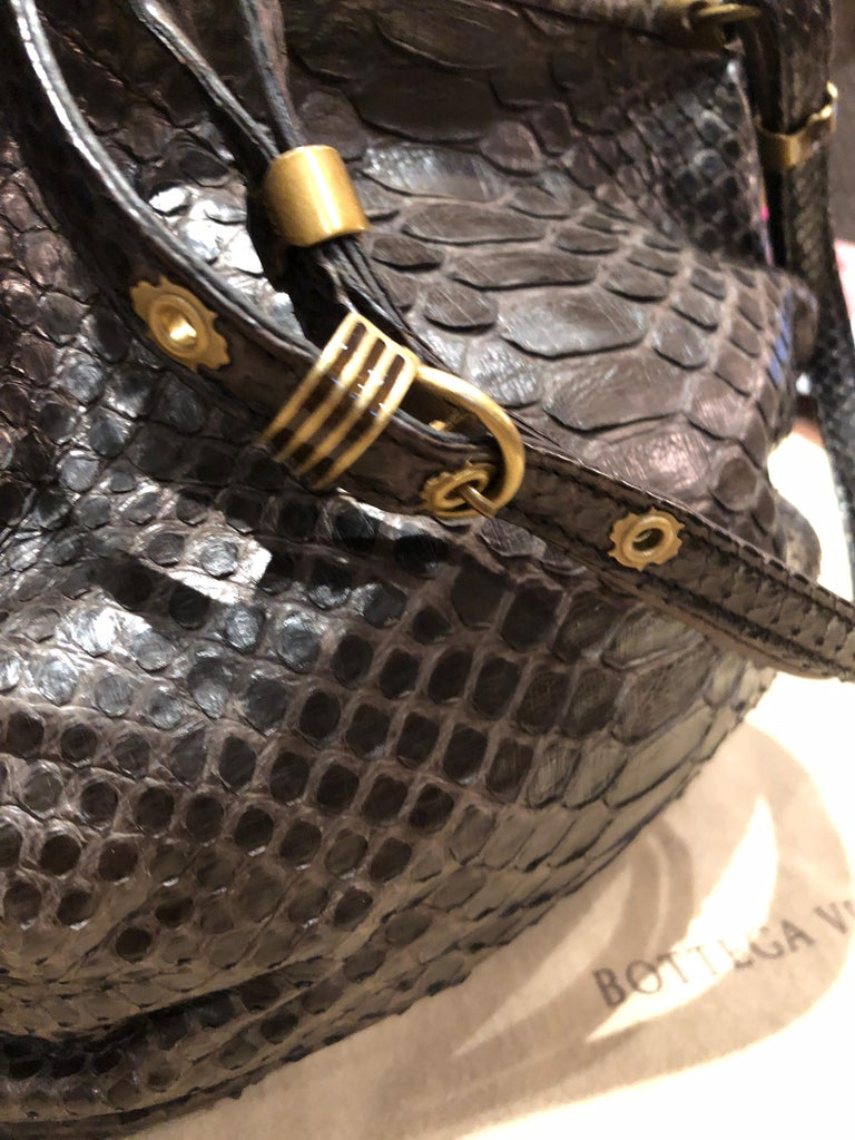 Soft handmade Ayers Bottega Veneta Kari frame naturally dyed and untreated brown snakeskin baguette having push lock closure, rope trim in brushed antique gold, and flat adjustable straps to create a shoulder bag. The cocoa colored suede lining has