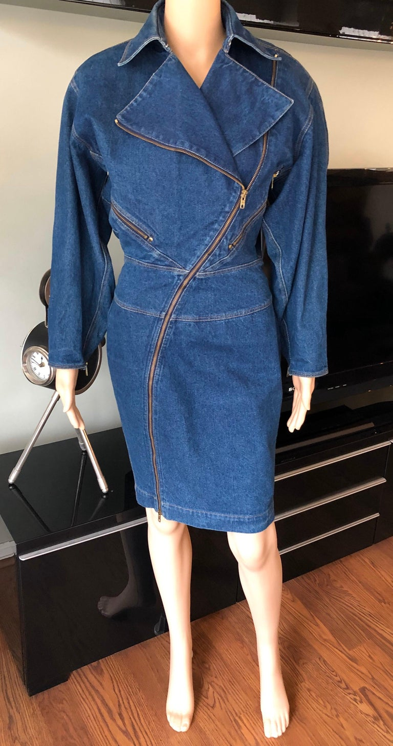 Azzedine Alaia 1980's Vintage Motorcycle Denim Coat Dress  Azzedine Alaia denim dress featuring full length asymmetrical zip closure in front, duel zip pockets at back, dolman sleeves with zippers on the cuffs and pointed collar. Please note the