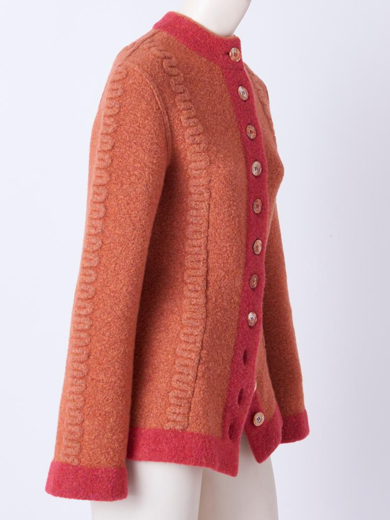 Azzedine Alaia, boiled wool, fitted cardigan in tones of coral, having a raised, pattern detail along the front and center sleeves. Mother of Pearl button closures.