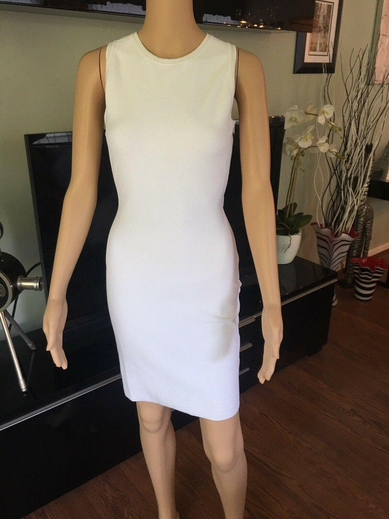Azzedine Alaia Fitted Open Back Dress  White Alaïa sleeveless textured bodycon dress featuring scoop neckline, crossover straps at open back and concealed zip closure at side seam.  All Eyes on Alaïa  For the last half-century, the world's most