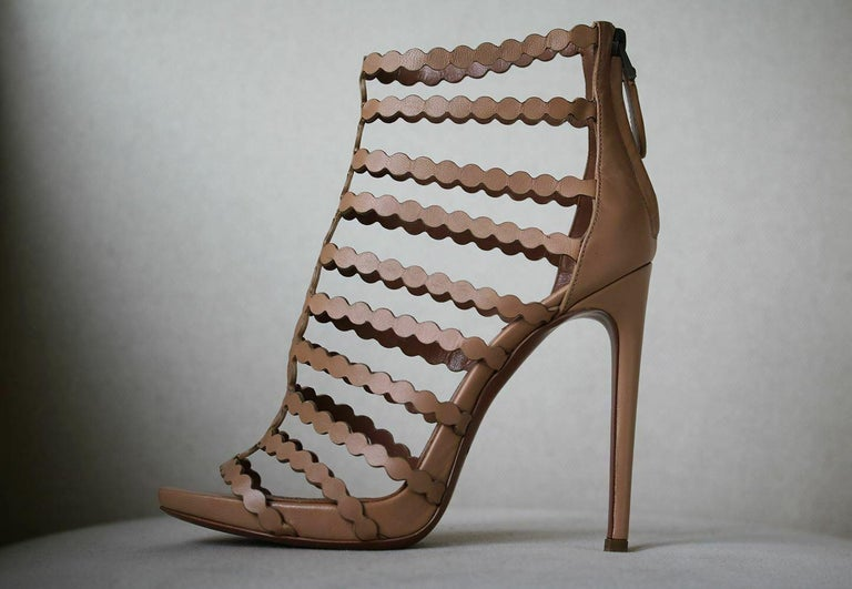 Neutral-hued sandals are supremely versatile. This pair by Alaïa is crafted in Italy using the label's signature laser-cutting technique. Heel measures approximately 115mm/ 4.5 inches with a 20mm/ 1 inch platform. Sand leather. Zip fastening along