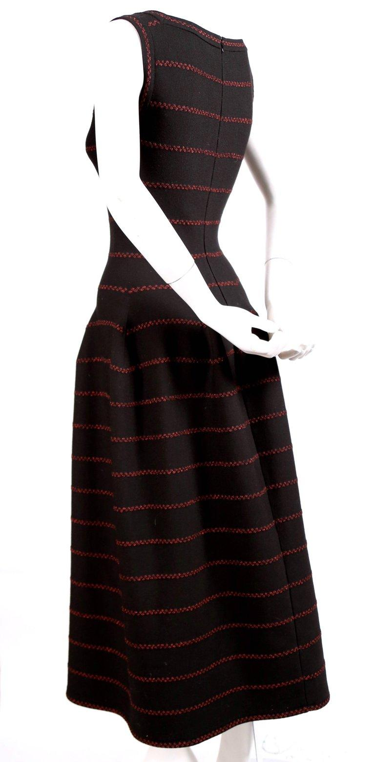 Long black knit dress with red lurex detail designed by Azzedine Alaia. Square boat neckline. Beautiful seaming creates the full skit which ends at a very flattering length above the ankle. French size 40 which fits a US 4-6. Approximate
