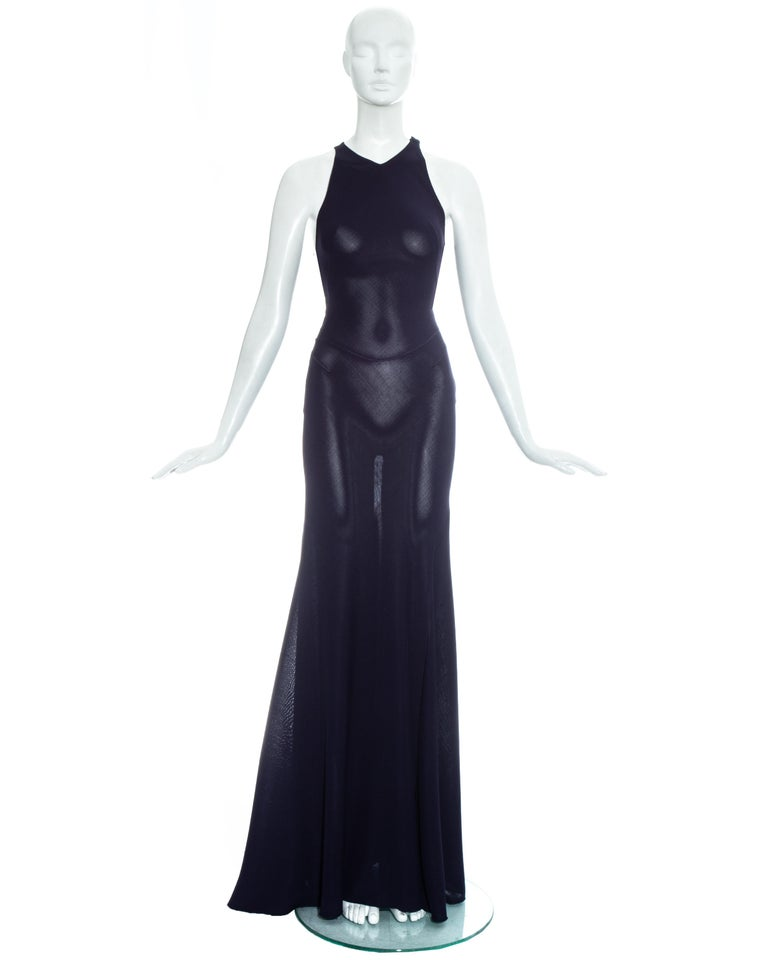 Azzedine Alaia; navy blue knitted rayon maxi dress with body conturing overlocked seams and flared maxi skirt. Invisible zip fastening and two hook and eye closures on shoulder.   Fall-Winter 2001