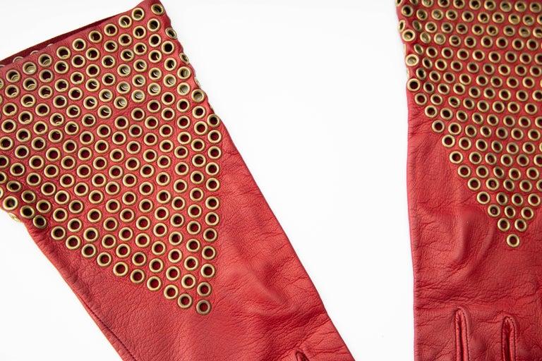 Azzedine Alia, Circa: 1980's oxblood leather gloves with bronze appliquéd grommets.  Length: 10, width: 5