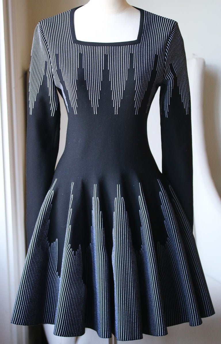Azzedine Alaïa black and white stretch-knit wool fit-flare dress. Features contrast white stitched line-design throughout the top and skirt of the dress. Square-neck. Long-sleeve. Concealed zip down the back. Colour: black and white. Made in Italy.