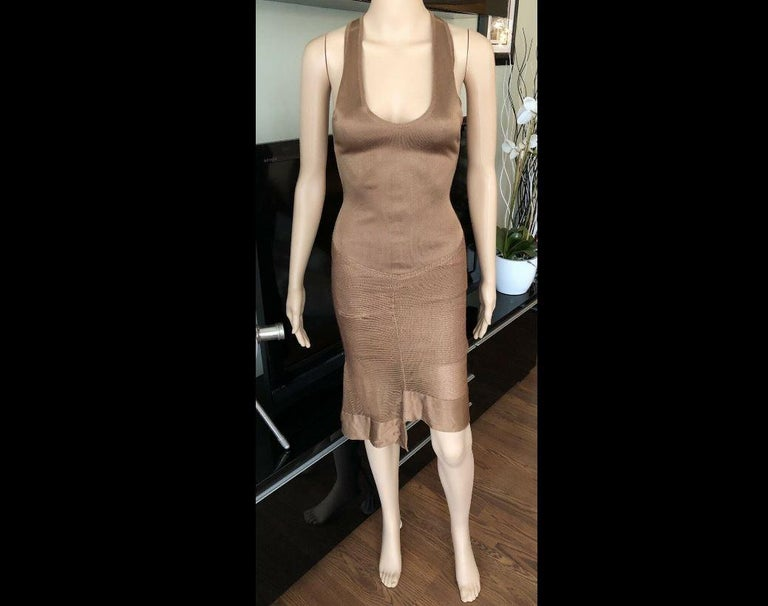 Alaïa sleeveless midi dress with scoop neck, rib knit trim and snap closures at back.  All Eyes on Alaïa  For the last half-century, the world's most fashionable and adventuresome women have turned to Azzedine Alaïa for body-enhancing clothes that