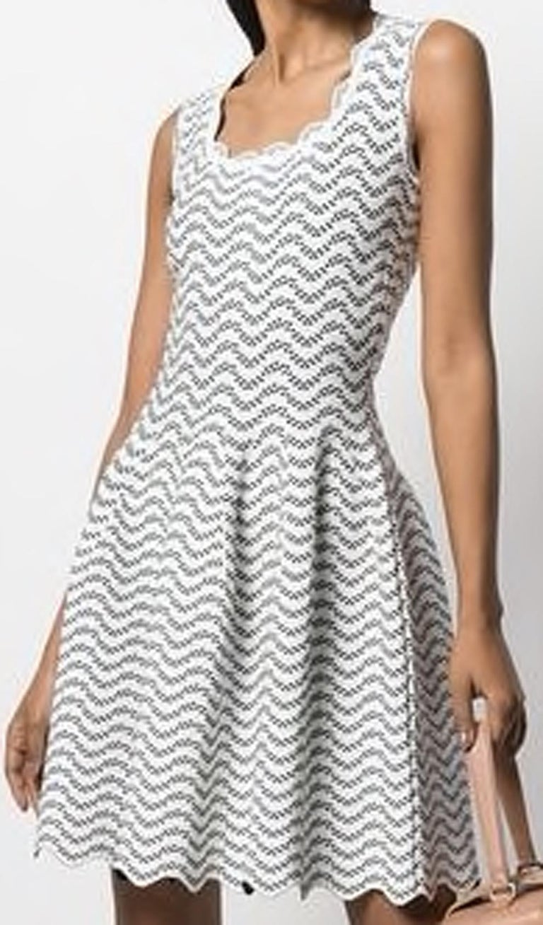 Azzedine Alaia flared dress featuring a white and black geometric pattern, a scalloped neck, an invisible back zip fastening, a sleeveless design, a fitted waist, a flared skirt, a short length, a scalloped hem.   In excellent vintage condition.