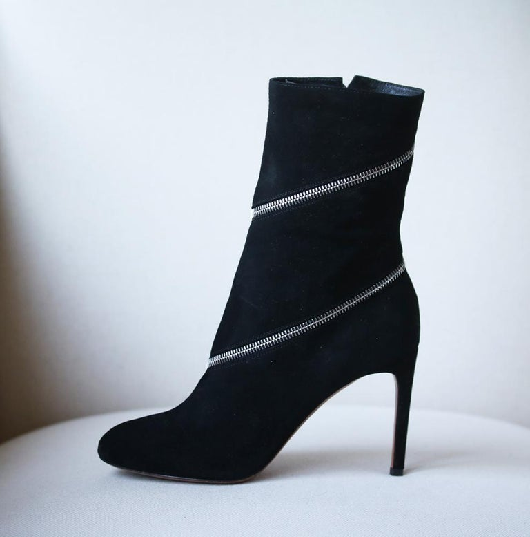 Alaïa's edgy suede boots have a fully functioning zip fastening that wraps around the front and ankle. Heel measures approximately 90mm/ 3.5 inches.  Black suede. Zip fastening along ankle and front. Does not come with a box.    Size: EU 38 (UK 5,