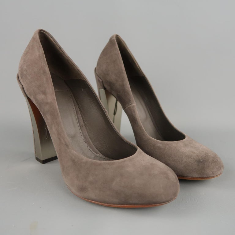 B BRIAN ATWOOD pumps come in taupe gray suede with a round toe and chunky heel with silver tone metal panel. With box. Made in Italy.   Excellent Pre-Owned Condition. Marked: 7.5   Measurements:   Heel: 4 in.