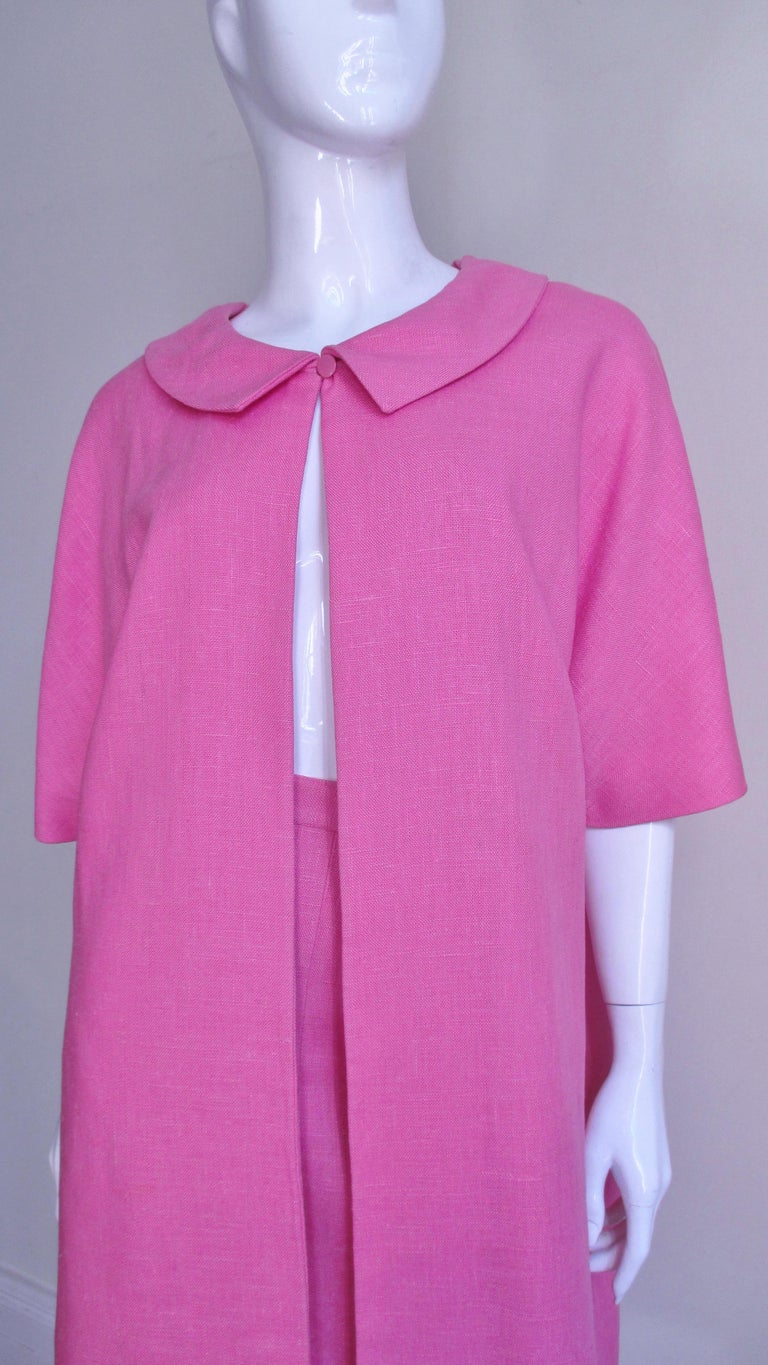 A pretty bight pink linen dress and coat set from B H Wragge.  It consists of a straight skirt with a small waistband and a coat with a collar, elbow length sleeves and side seam pockets.  The coat is lined in white silk with matching pink abstract